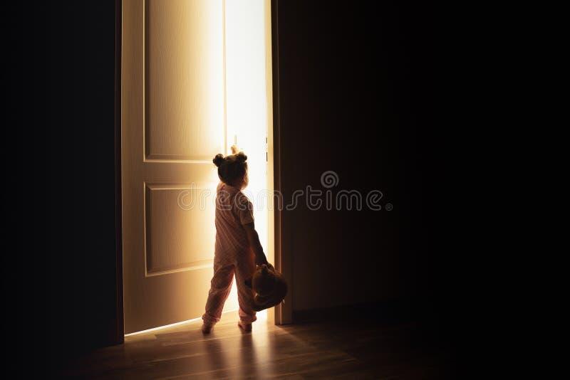 A menina abre a porta à luz na escuridão fotos de stock royalty free