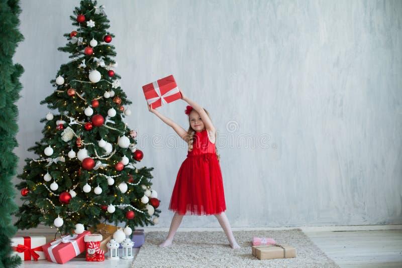 A menina abre presentes do Natal na casa de férias do ano novo de árvore de Natal foto de stock