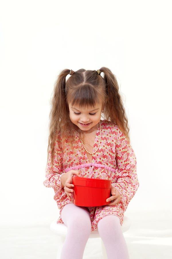 A menina abre seu presente fotos de stock