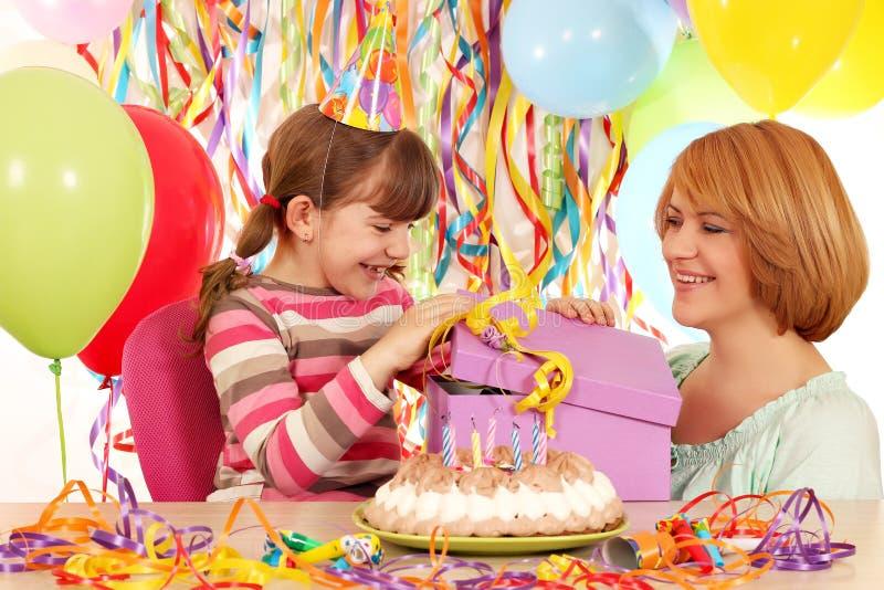 A menina abre um presente de aniversário fotos de stock royalty free