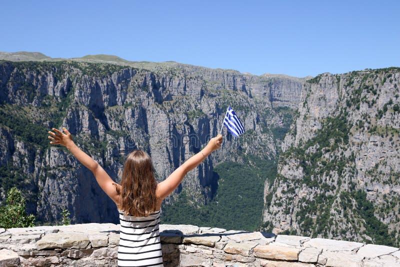 A menina acena com uma bandeira grega no desfiladeiro Zagoria de Vikos fotos de stock royalty free