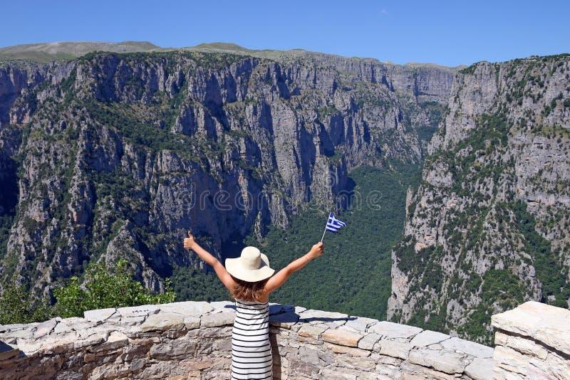 A menina acena com uma bandeira grega no desfiladeiro Zagoria de Vikos foto de stock royalty free