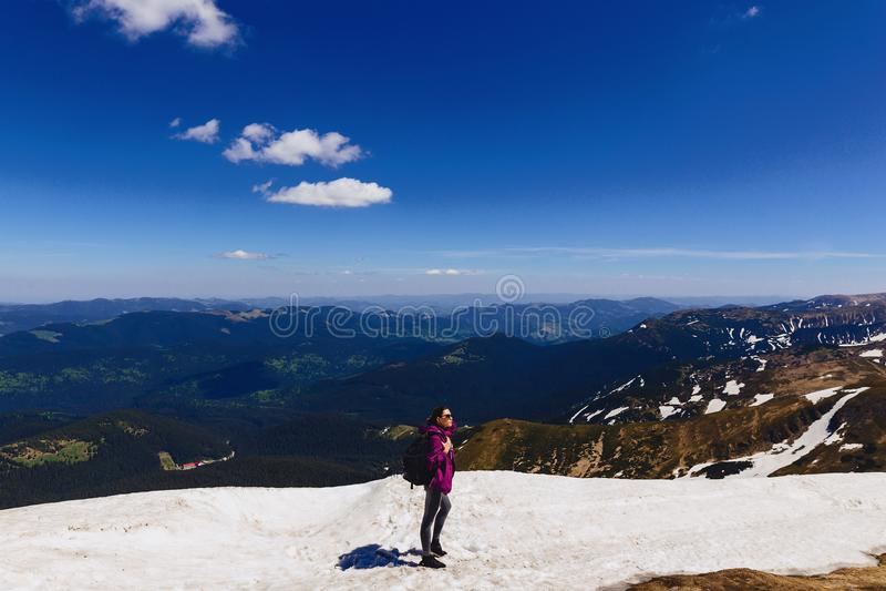 menina acolhedor na montanha na neve imagens de stock