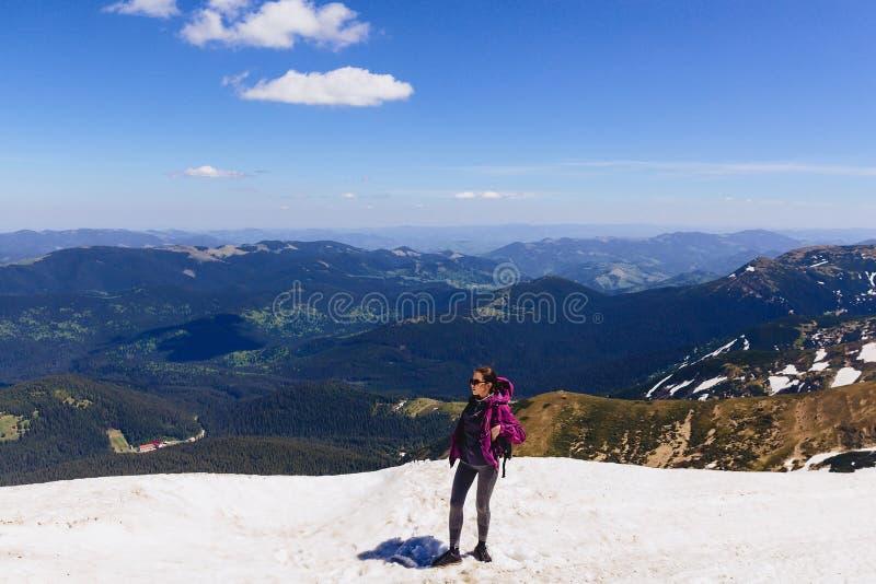 menina acolhedor na montanha na neve imagem de stock royalty free