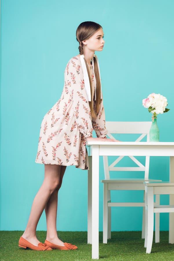 menina adolescente à moda com as tranças que estão na tabela com o ramalhete das flores imagem de stock royalty free