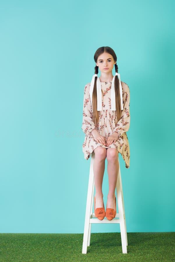 menina adolescente à moda no vestido do verão com as tranças que sentam-se no tamborete foto de stock royalty free