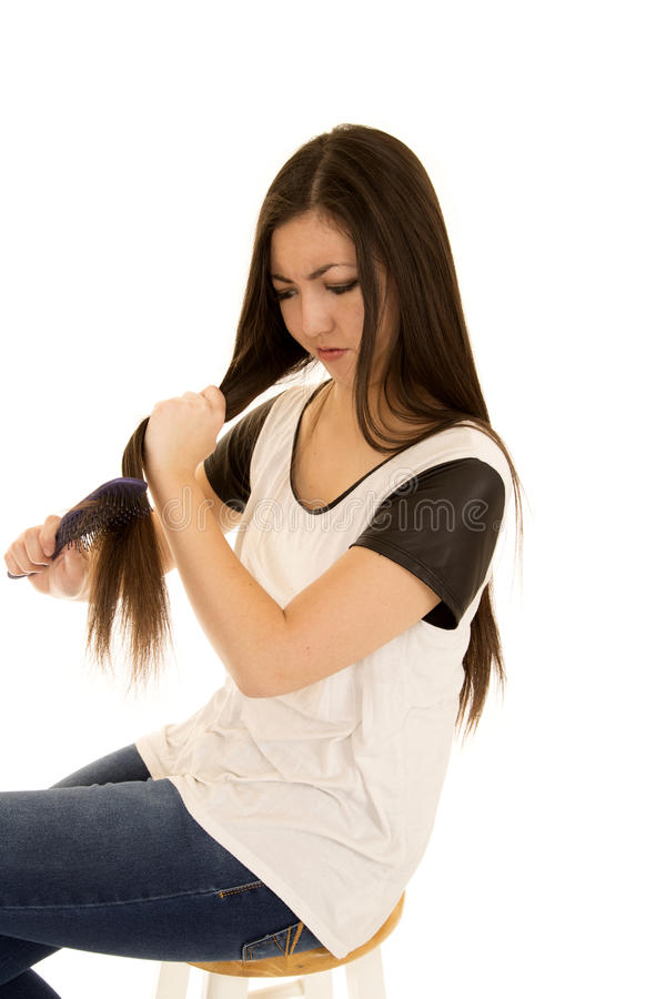 A menina adolescente étnica bonito frustrou a escovadela de seu cabelo foto de stock