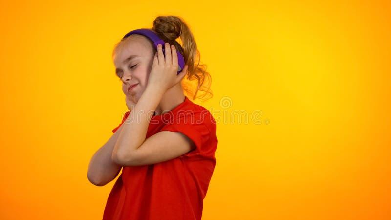 Menina adolescente adorável que escuta a música favorita nos fones de ouvido e que dança, passatempo fotos de stock royalty free