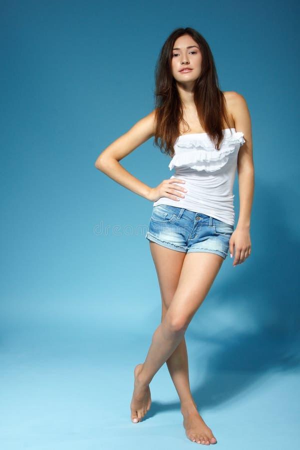 Menina adolescente alegre bonita no short de brim e na parte superior branca, completamente fotografia de stock