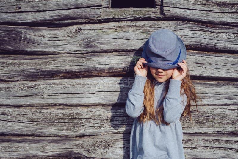 Menina adolescente alegre na roupa ocasional e no chapéu azul que levantam por uma parede de madeira Estilo de vida ativo Forma d imagens de stock