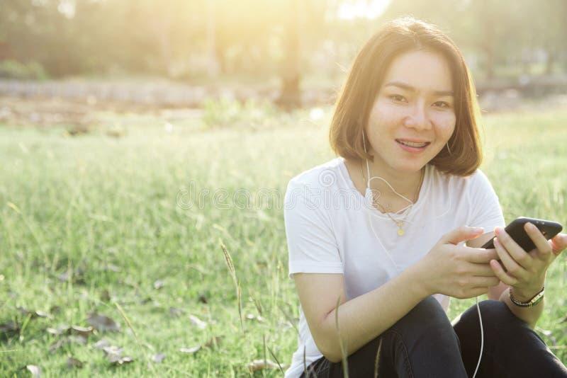 A menina adolescente asiática do cabelo curto aprecia com música do telefone celular fotos de stock