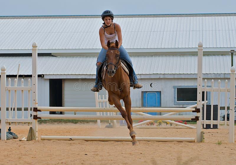 Menina adolescente atlética que salta um cavalo sobre os trilhos. imagem de stock