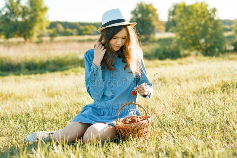 Menina adolescente atrativa que come a morango Fundo da natureza, paisagem rural, prado verde, estilo country fotografia de stock royalty free