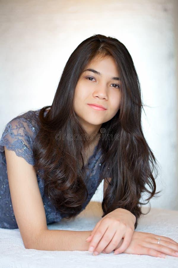 Menina adolescente biracial bonita que encontra-se para baixo, relaxando fotos de stock royalty free