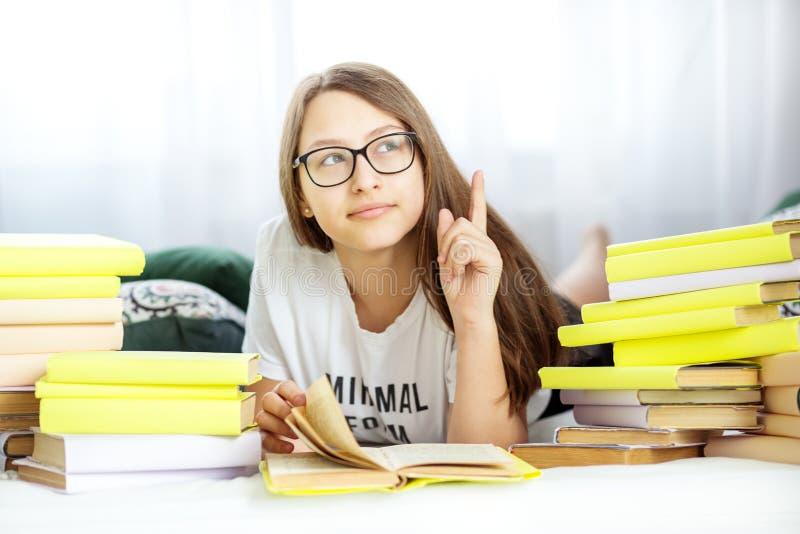 A menina adolescente bonita aprende e medita na sala Conceito da educação, do passatempo, do estudo e do dia do livro do mundo imagens de stock royalty free