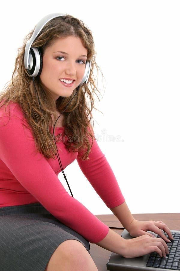 Menina adolescente bonita com auscultadores e portátil imagens de stock