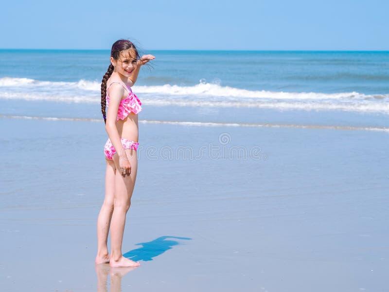 Menina adolescente bonita com o cabelo longo que veste na posição cor-de-rosa do roupa de banho na praia e que olha na distância imagens de stock