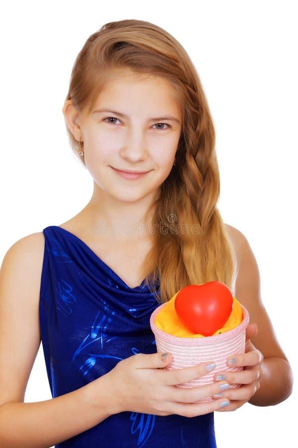 Menina adolescente bonita de sorriso com um presente e um coração vermelho simbólico imagens de stock royalty free