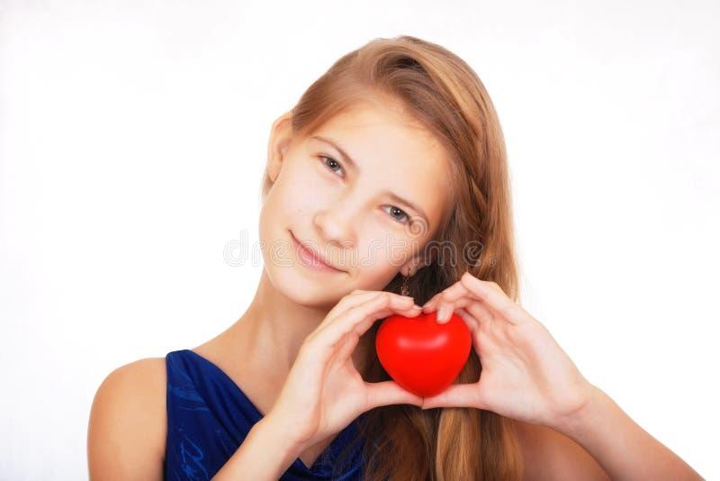 Menina adolescente bonita de sorriso com um presente simbólico sob a forma de um coração vermelho fotografia de stock royalty free