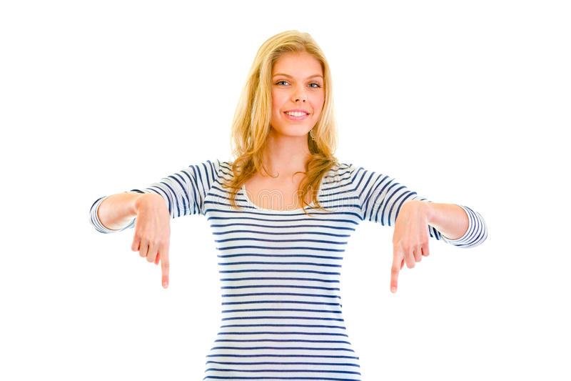 Menina adolescente bonita de sorriso que aponta os dedos para baixo fotografia de stock royalty free