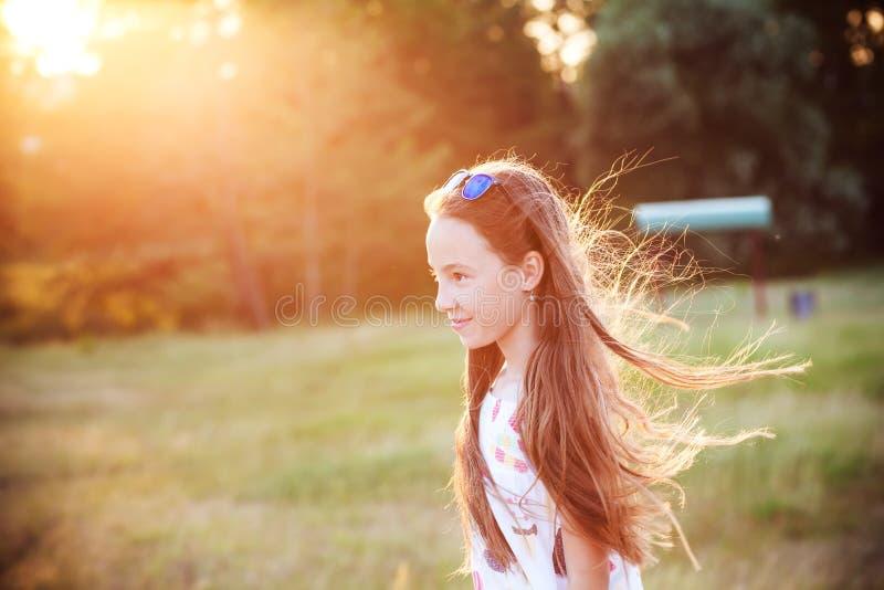 A menina adolescente bonita está apreciando a natureza no parque no por do sol do verão imagem de stock
