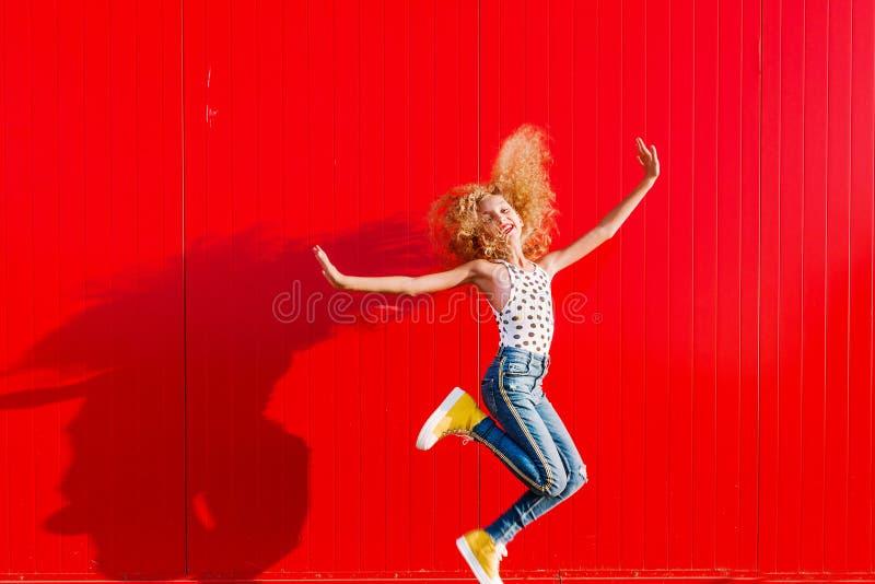 A menina adolescente bonita faz um salto na perspectiva de uma parede vermelha fotos de stock royalty free