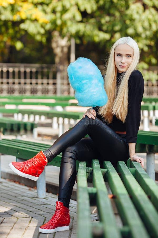 A menina adolescente bonita loura desportiva à moda nova com assento ciano-azul de doce-floss cruzou os pés no banco de parque em fotografia de stock
