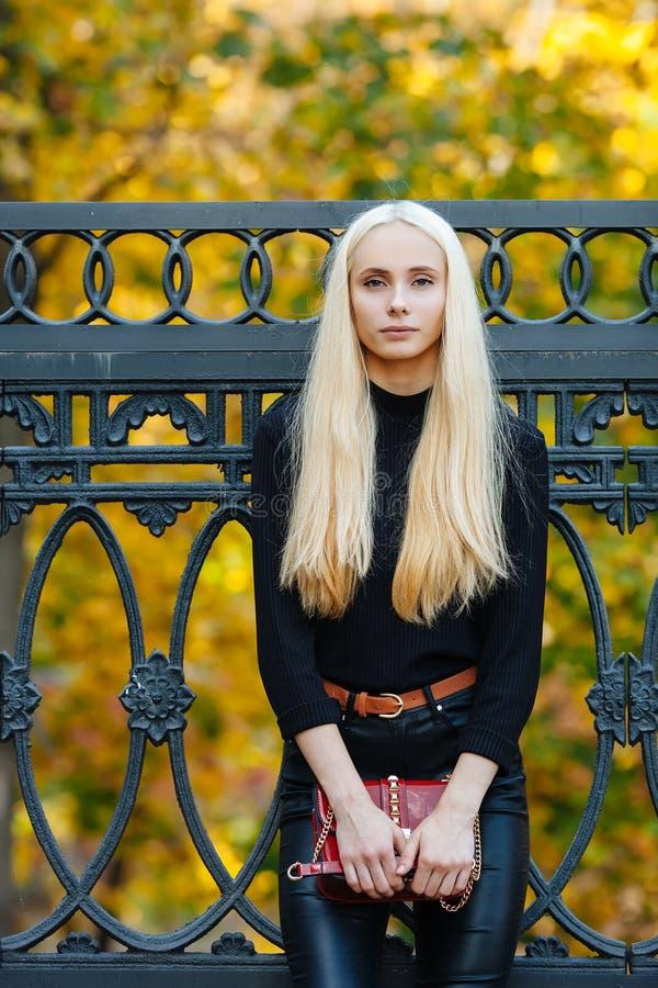 A menina adolescente bonita loura desportiva à moda nova no levantamento preto no parque em um dia dourado morno da queda contra  fotos de stock