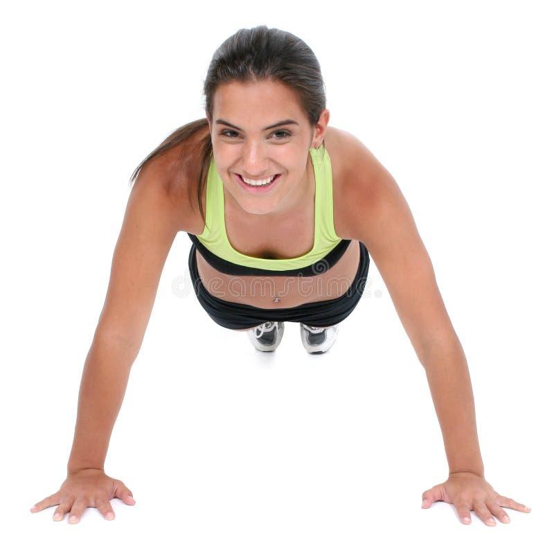 Menina adolescente bonita na roupa do exercício que faz Pushup imagem de stock