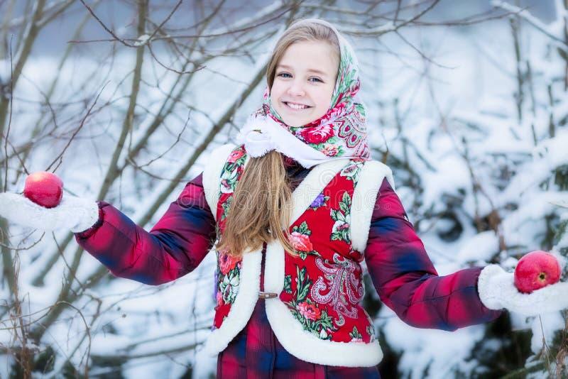 Menina adolescente bonita na roupa nacional do russo com as maçãs vermelhas nas mãos do inverno imagem de stock