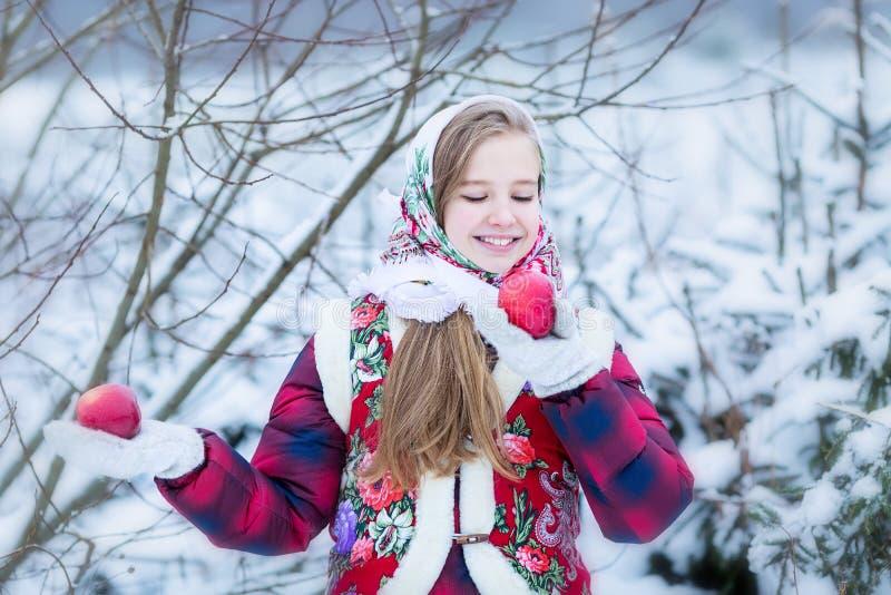 Menina adolescente bonita na roupa nacional do russo com as maçãs vermelhas nas mãos do inverno fotos de stock