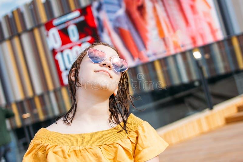 A menina adolescente bonita no cora??o cor-de-rosa deu forma a vidros com cabelo molhado aprecia f?rias de ver?o na cidade imagens de stock royalty free