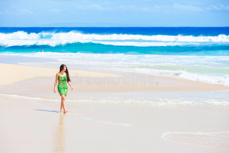 Menina adolescente bonita no vestido verde que anda ao longo da praia havaiana imagens de stock royalty free
