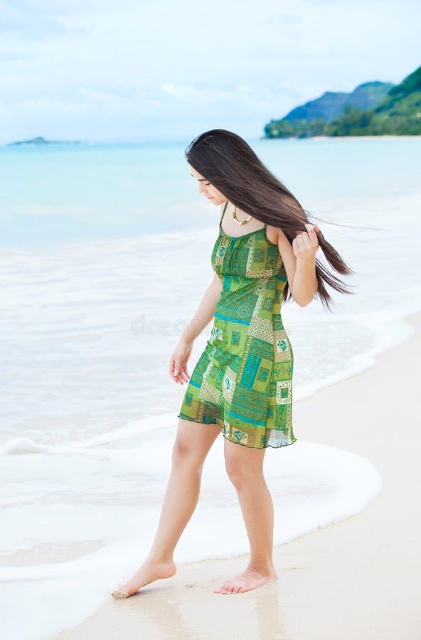 Menina adolescente bonita que mergulha os dedos do pé na água na praia tropical imagem de stock