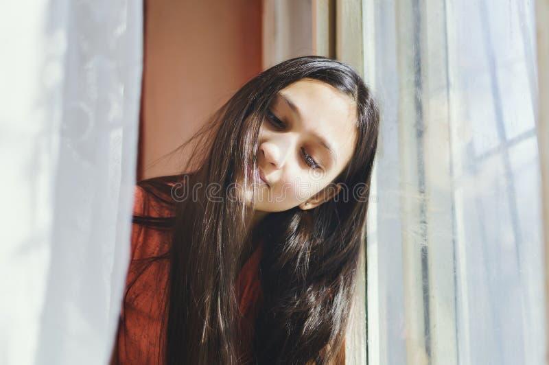 Menina adolescente bonita que senta-se pela janela foto de stock royalty free