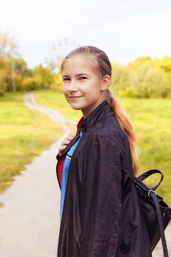 Menina adolescente bonito com mala a tiracolo que anda no parque do outono fotos de stock royalty free