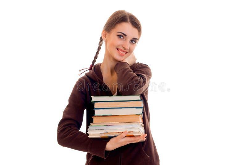Menina adolescente bonito com tranças que sorri e que guarda um livro em suas mãos imagem de stock