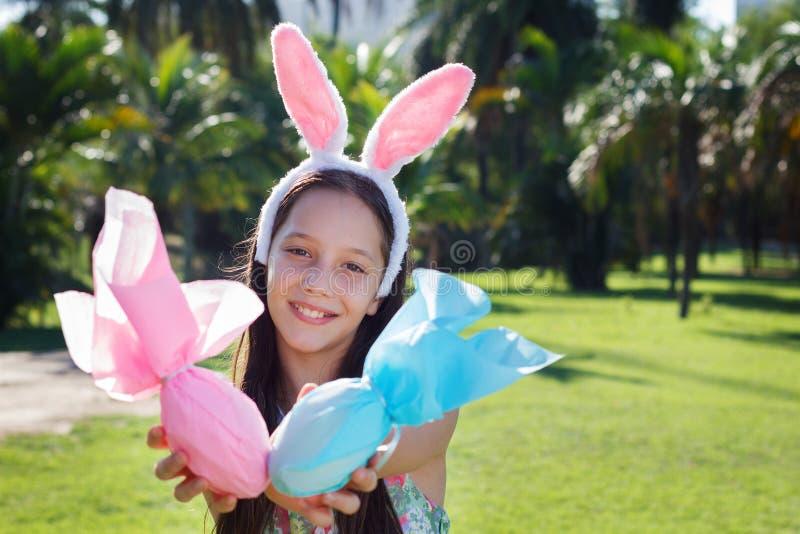 Menina adolescente bonito de sorriso com as orelhas de coelho que guardam o chocolate da Páscoa imagem de stock royalty free