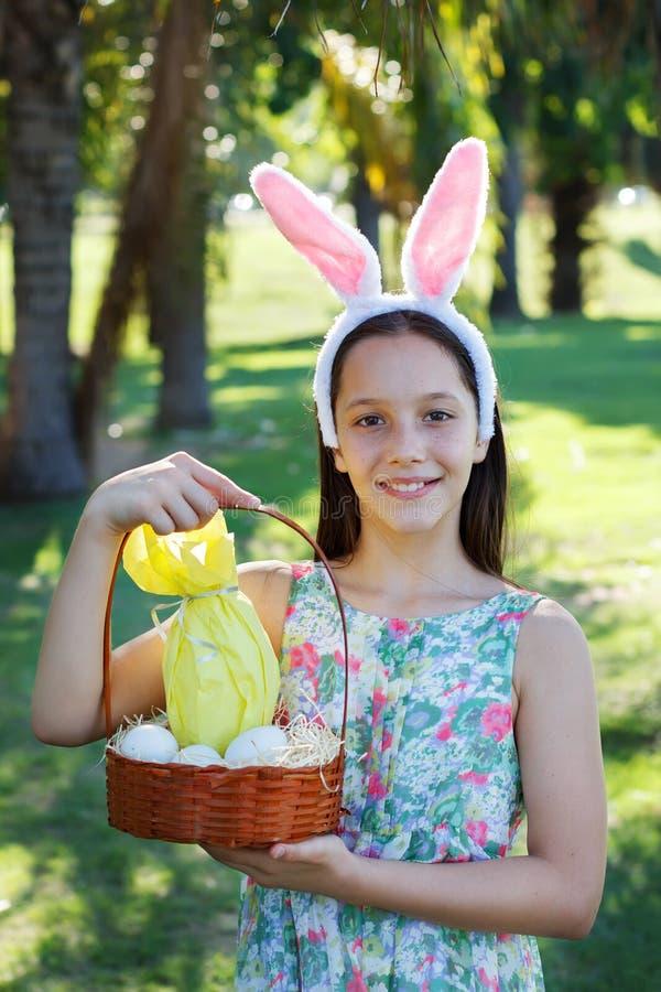 Menina adolescente bonito de sorriso com as orelhas de coelho que guardam ovos de chocolate fotografia de stock