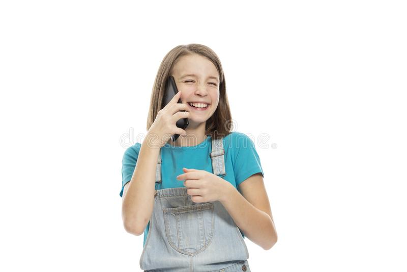 Menina adolescente bonito em macacões da sarja de Nimes que fala no telefone e no riso Isolado em um fundo branco fotos de stock