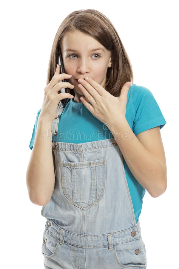 Menina adolescente bonito em macacões da sarja de Nimes que fala no telefone Isolado em um fundo branco foto de stock royalty free
