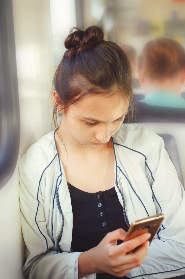 A menina adolescente bonito monta em um trem bonde e olha em um smartphone fotografia de stock