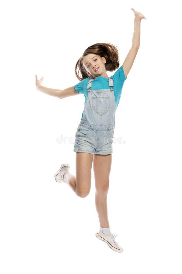 Menina adolescente bonito no salto das calças de brim Isolado em um fundo branco fotografia de stock royalty free