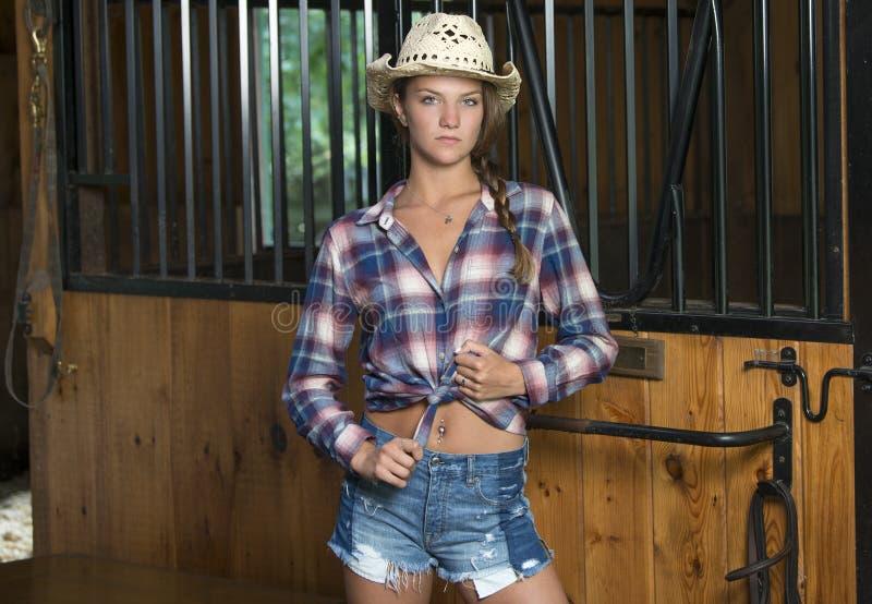 A menina adolescente bonito no vestuário da equitação levanta no celeiro foto de stock royalty free