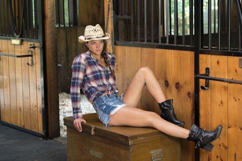 A menina adolescente bonito no vestuário da equitação levanta no celeiro imagens de stock