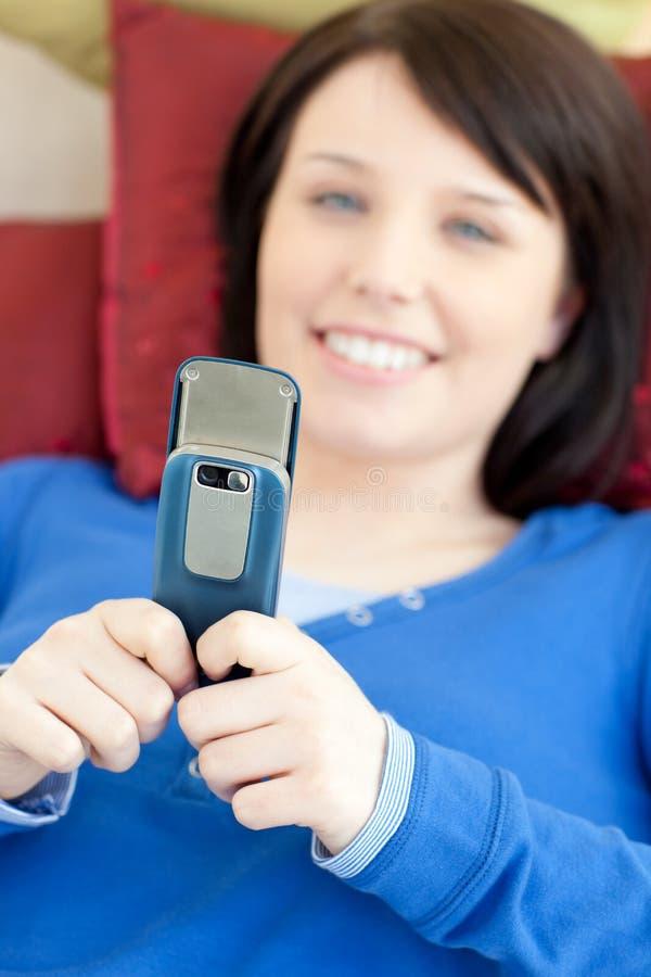 Menina adolescente bonito que emite um texto que encontra-se em um sofá imagens de stock
