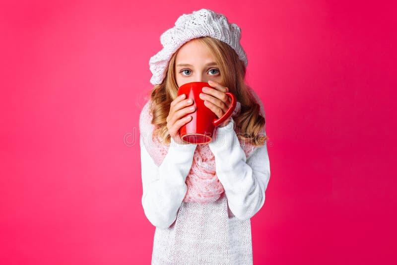 A menina adolescente bonito, tomando sol com uma caneca de chá, vestiu-se em um KNI cor-de-rosa imagem de stock