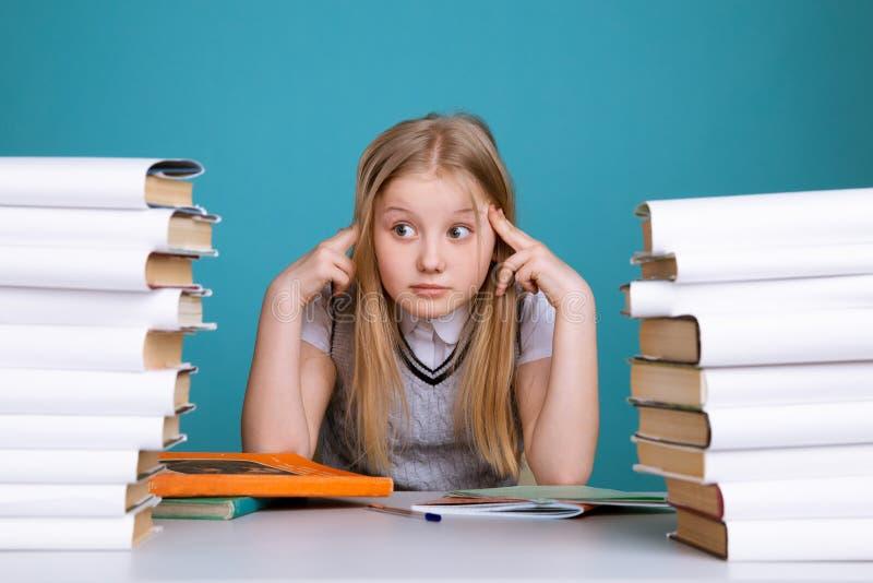 Menina adolescente cansado com os livros no fundo de uma administração da escola que olha a câmera Espa?o para o texto imagens de stock royalty free