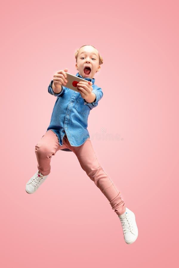Menina adolescente caucasiano feliz nova que salta com o telefone no ar, isolado no fundo cor-de-rosa do estúdio fotos de stock