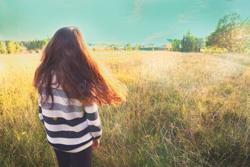 A menina adolescente com cabelo fraco marrom longo fica para trás foto de stock